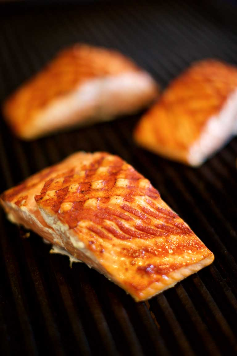Farmed salmon pieces cooking on a bbq.