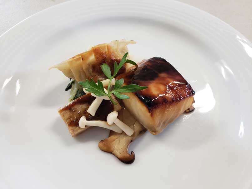 Farmed sablefish and mushrooms on a plate.