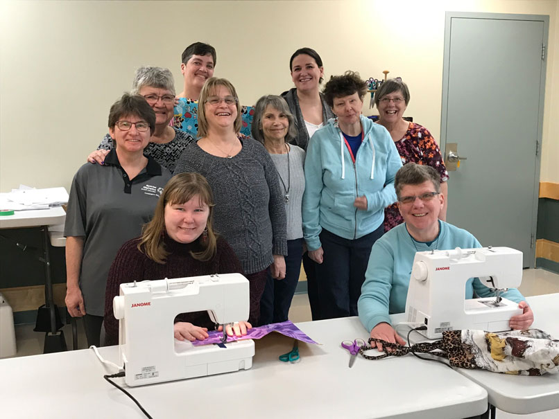 A group of ladies using sewing machines to make clothes for charity.