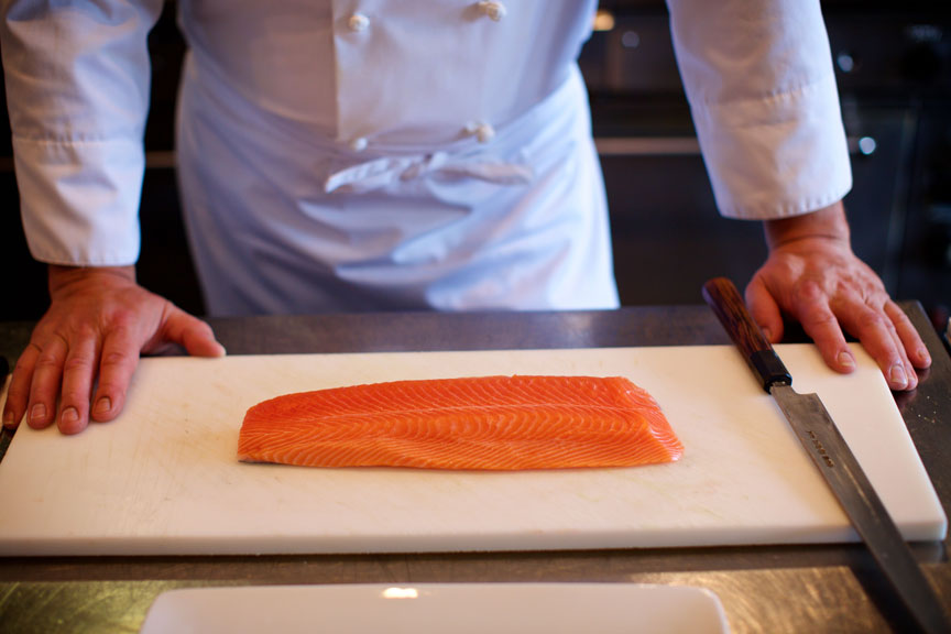 A chef looking at a piece of farmed salmon.